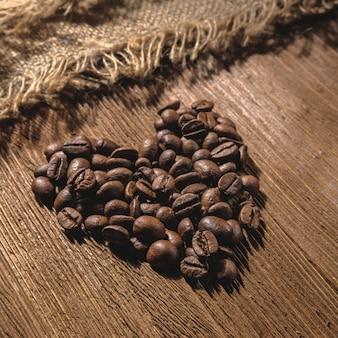 大きなハートは、テクスチャード加工された木製のテーブルの上に、正方形のプロポーションと低いキーでコーヒー豆から配置されています。
