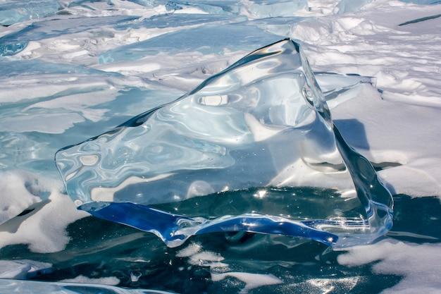 Большая льдина, растаявшая на солнце, стоит на льду байкала с отражениями и искажениями в прозрачном льду.