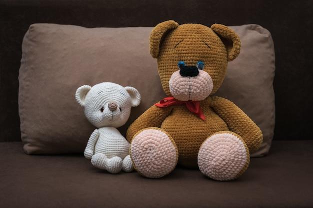 大きなニットのクマが小さなクマを茶色のソファに抱きしめます。美しいニットのおもちゃ。