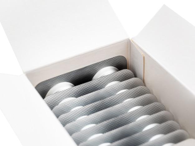 Большое количество капсул в серебряной упаковке находятся в картонной коробке, изолированно, крупным планом.