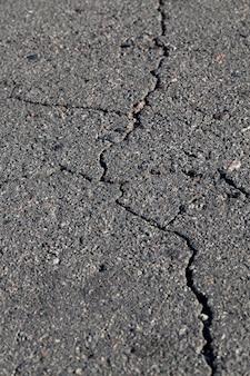 Большое количество трещин на темном асфальте, детали транспортной инфраструктуры.