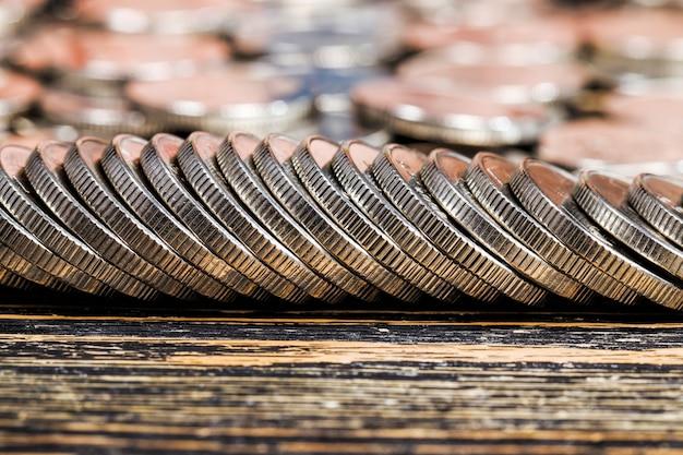 많은 수의 은색 금속 동전이 나무 테이블에 쌓여 있고, 국가에서 지불에 사용되는 법정 입찰, 아름다운 동전 근접 촬영 같은 동전 가치 외화
