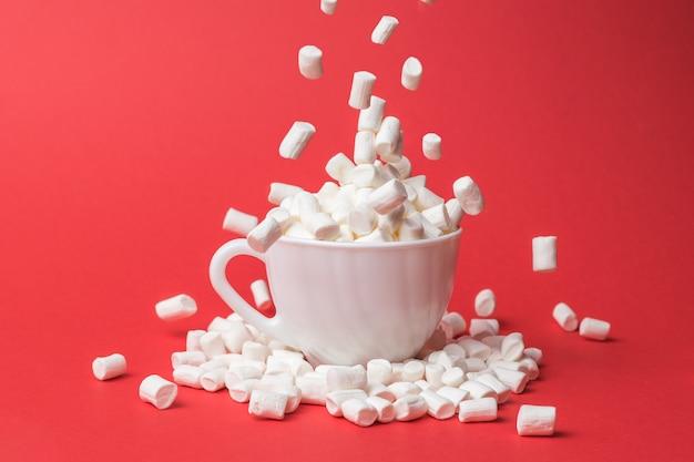 В белую чашку выпадает большое количество мелких зефиров. сладкое угощение.