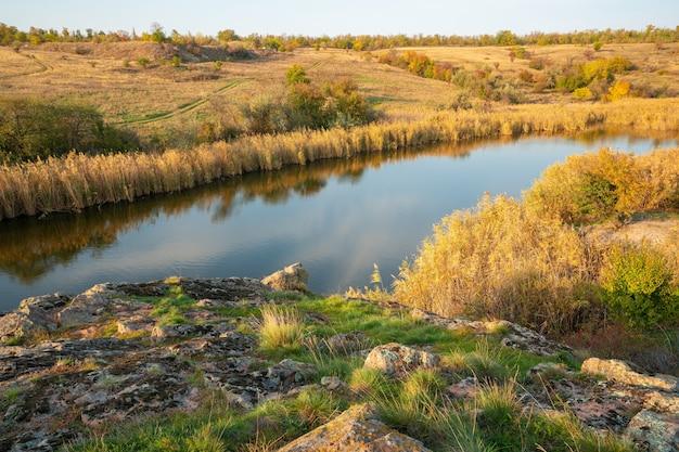 Большое количество каменных минералов, покрытых зеленой растительностью, лежащих над небольшой речкой в живописной украине и ее прекрасной природе.