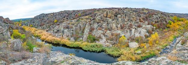 작은 강 위에 놓인 녹색 식물로 덮인 수많은 석재 광물