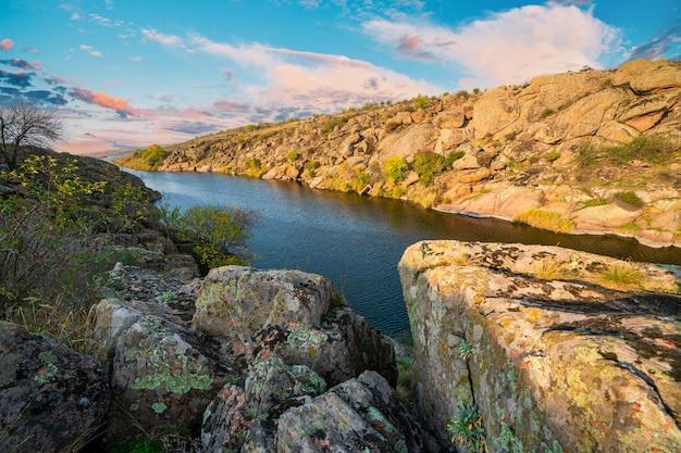 Большое количество каменных минералов, покрытых растительностью, лежащих над небольшой речкой в живописной украине.