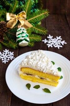 エアクリームを飾る繊細なスポンジケーキの大部分。木製の背景にお祝いのデザート