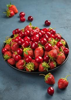 진한 파란색 배경에 체리와 딸기가 섞인 큰 접시. 측면 보기, 수직입니다.