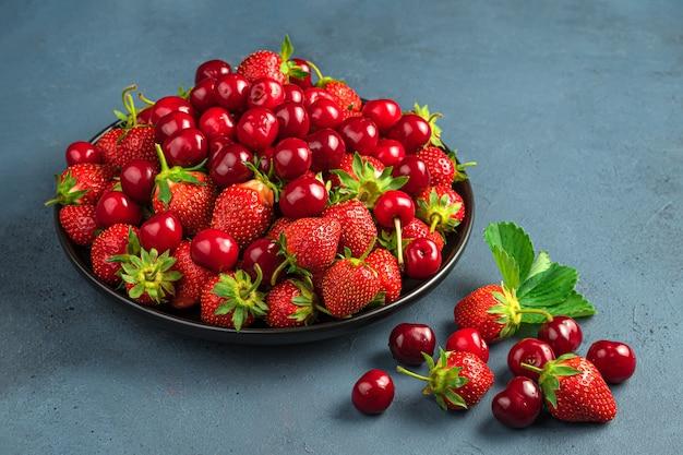회색 파란색 배경에 신선한 체리와 딸기가 있는 큰 접시. 측면 보기, 클로즈업입니다.