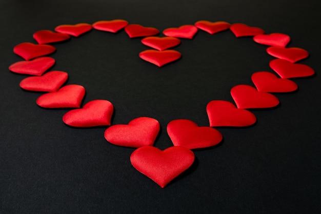 Большое красное сердце, выложенное из множества маленьких одинаковых красных шелковых сердечек на черном фоне