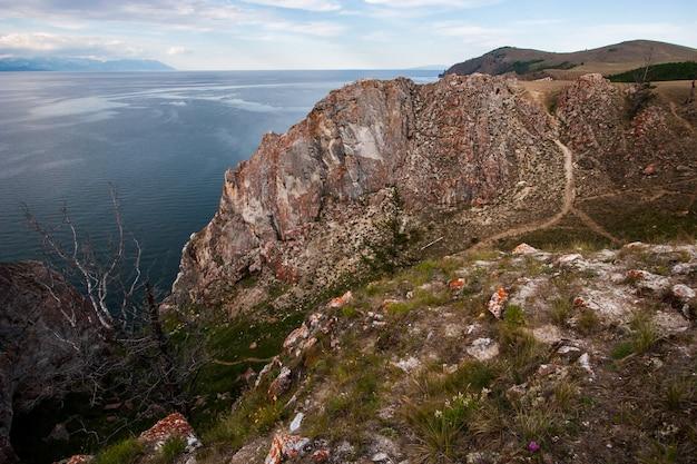 Большая скала на берегу байкала. есть тропинка к скале. есть сухое дерево. за горным озером в дымке.