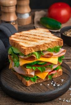 햄 치즈 토마토와 오이 근접 촬영 측면 보기와 함께 큰 샌드위치