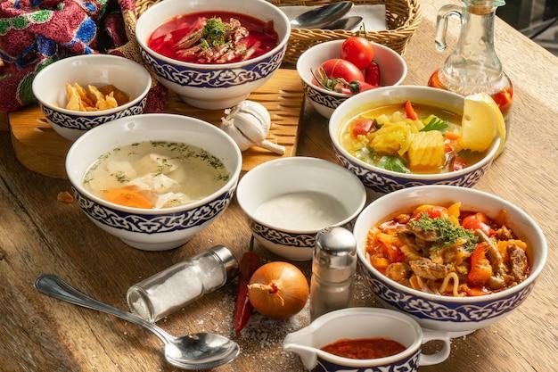 Большой набор разных восточных супов. борщ с говядиной и сметаной, лагман с бараниной и аджикой, куриный бульон шурпа и ухи с овощами.