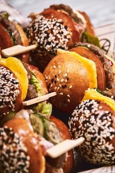 많은 햄버거, 치즈버거의 큰 세트가 테이블에 놓여 있습니다. 세스 패스트푸드. 음식 배경, 복사 공간입니다.