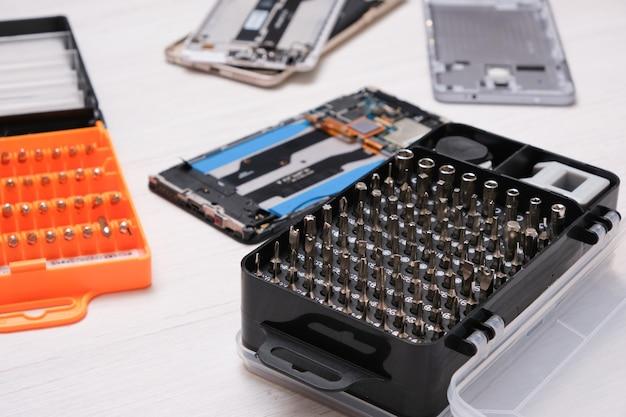 블랙박스에 있는 큰 드라이버 비트 세트와 나무 탁자에 있는 깨진 스마트폰, 집에서 전화 수리