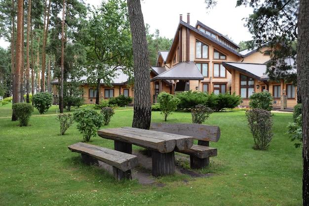 夏の公園にある大きなテーブルと荒削りの丸太の2つのベンチ。背景の木造家屋