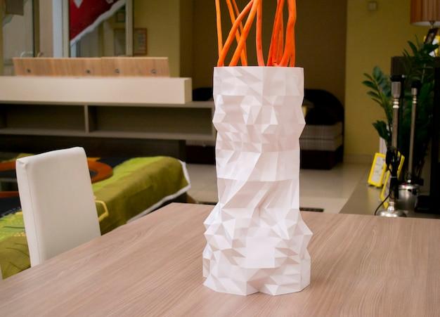 3d 프린터로 인쇄된 큰 흰색 꽃병이 테이블 위에 서 있습니다