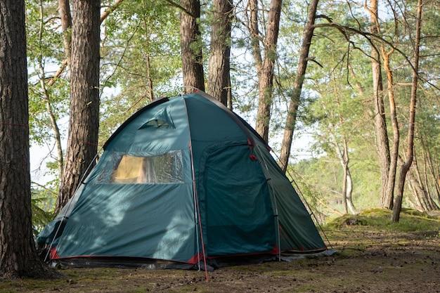 호수 옆 아름다운 숲의 캠프장에 대형 관광 텐트가 설치되어 있습니다.