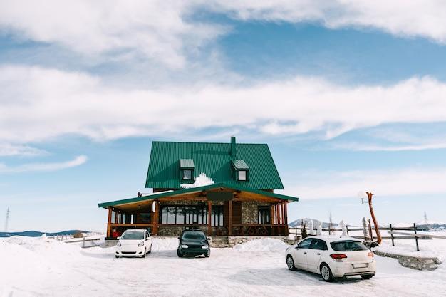 Большой двухэтажный дом с зеленой крышей и застекленной верандой и террасой зимой в