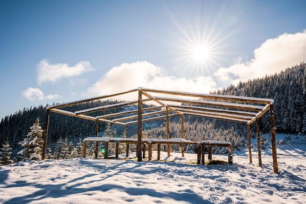 산 정상에있는 크고 덮이지 않은 전망대가 carpathians의 밝고 차가운 태양 빛을 받아 눈으로 덮인 하얀 초원 위에 서 있습니다.