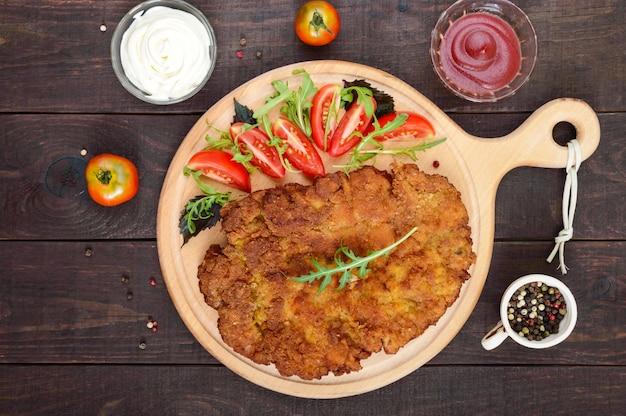 Большой венский шницель и салат из помидоров на разделочной доске на темном деревянном столе