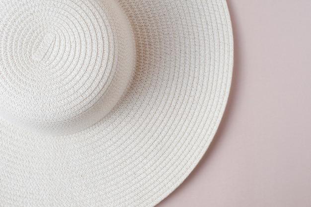 パステルベージュの背景に大きな白いビーチの女性の帽子。休暇、休暇、旅行、販売、ブラックフライデーの概念。