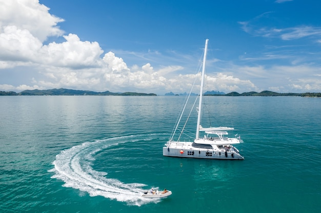 Большая белая парусная яхта и моторная лодка с людьми.