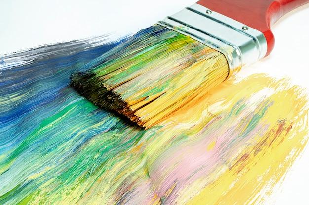 Большая деревянная художественная кисть рисует на холсте. техника рисования. яркие краски на холсте. хобби и творчество. картина.
