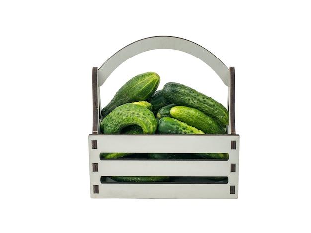 흰색 배경에 격리된 오이가 있는 큰 나무 상자. 야채의 신선한 작물입니다.