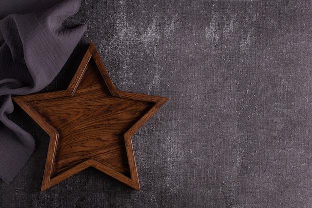 별 모양의 큰 나무 쟁반은 어두운 배경에 놓여 있습니다.