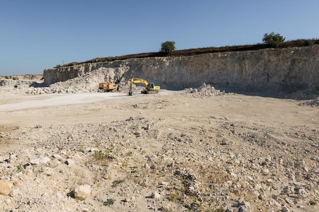 큰 노란색 추적 굴착기가 채석장에서 암석을 채굴하고 있습니다. 프리미엄 사진