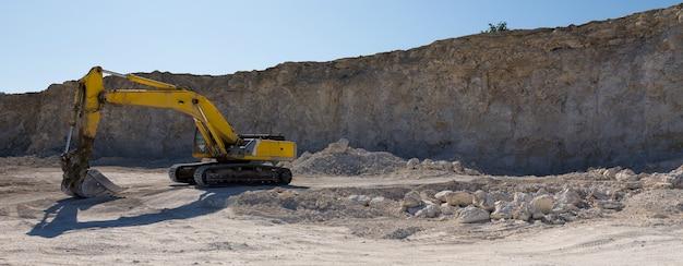 大きな黄色のトラック掘削機が採石場で岩を採掘しています。