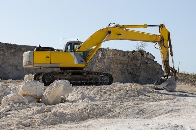 큰 노란색 추적 굴착기가 채석장에서 암석을 채굴하고 있습니다.