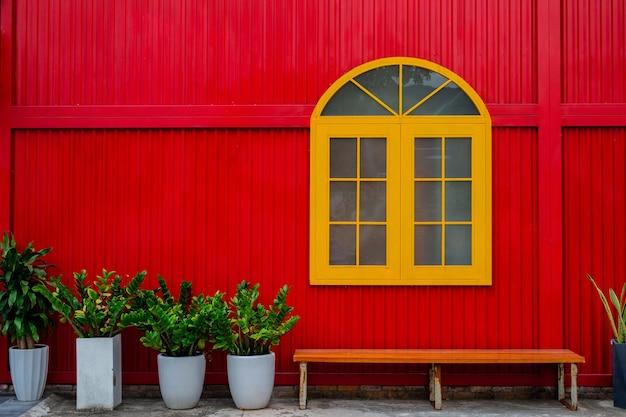 大きな黄色い窓、植物が植えられた植木鉢、街の通りの赤い金属の壁に面したベンチ。閉じる