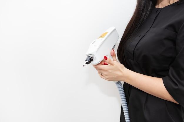 Мастер лазерной эпиляции держит в руках аппарат для лазерной эпиляции. удаление волос на всех участках тела. аппарат для удаления волос. место для надписи.