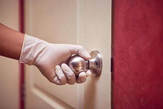 Рука человека в латексной перчатке открывает дверь, нажав на ручку