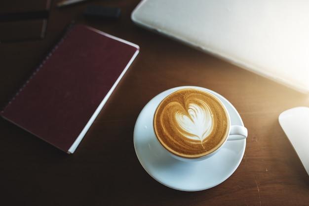 Кофе латте и ноутбук на столе.