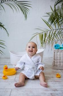 목욕 가운을 입은 웃고 있는 아기 소녀가 아기 목욕 옆에 앉아 있습니다. 아동 위생