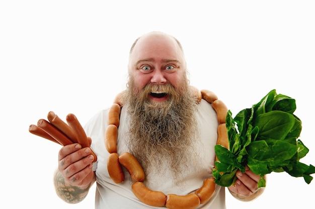 Смеющийся бородатый мужчина с большим весом, одетый в груду сосисок на шее, показывает в камеру сосиски и зелень. изолированный портрет на белой предпосылке.