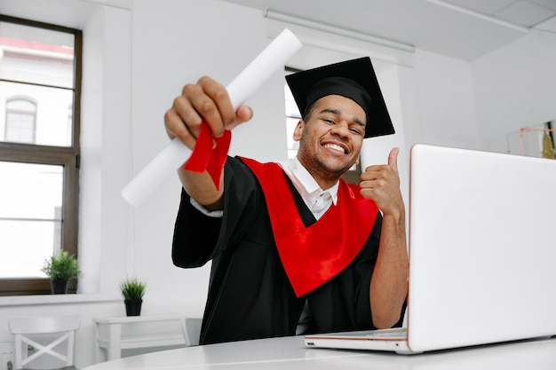 Смеющийся темнокожий студент в выпускном платье и квадратной кепке, который рад закончить учебу, показывает свой долгожданный диплом о виртуальном выпуске и церемонии созыва. класс 2021 года.