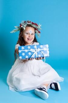 흰 드레스에 웃는 소녀, 화환과 운동화를 입고 바닥에 앉아