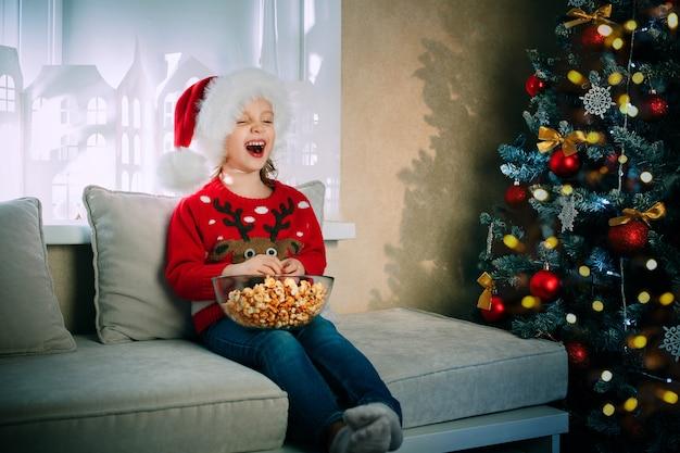 クリスマスイブにサンタクロースの帽子をかぶった笑う女の子は、テレビを見ながらポップコーンを楽しんでいます