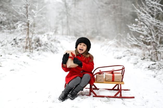 雪の降る寒い日に、笑う少女が冬の森のそりに座っている