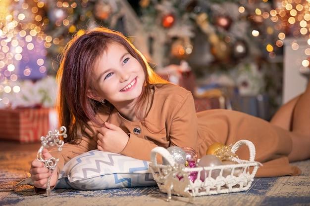 Смеющаяся девушка лежит на полу с новогодним украшением в руках на фоне елки.