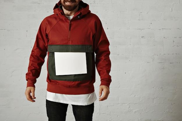 白の大きなフロントポケットに無地の白い紙を置いたスタイリッシュな赤とグレーのアノラックの笑い男