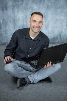 웃고 있는 청년이 손에 노트북을 들고 바닥에 앉아 있다