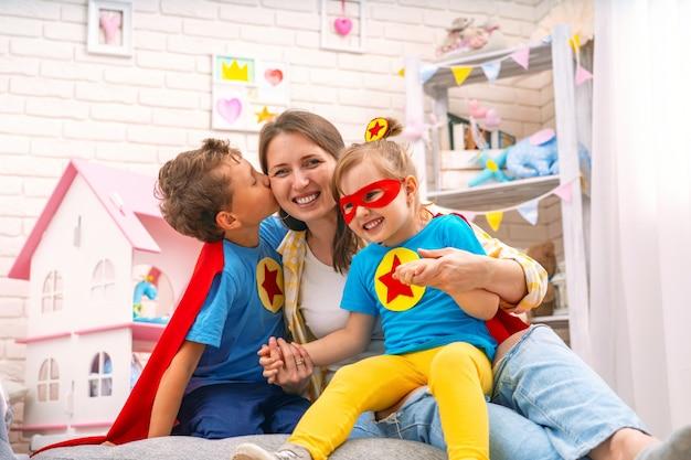 Смеющаяся молодая женщина играет в игры супергероев со своими детьми