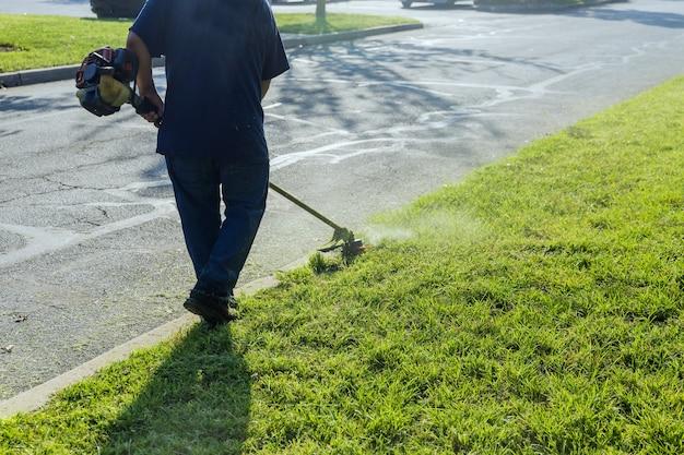 잔디 깎는 기계가 잔디 깎는 기계를 손에 들고 있는 도시 노동자가 근처 잔디밭에서 신선하고 푸른 잔디를 깎고 있습니다.