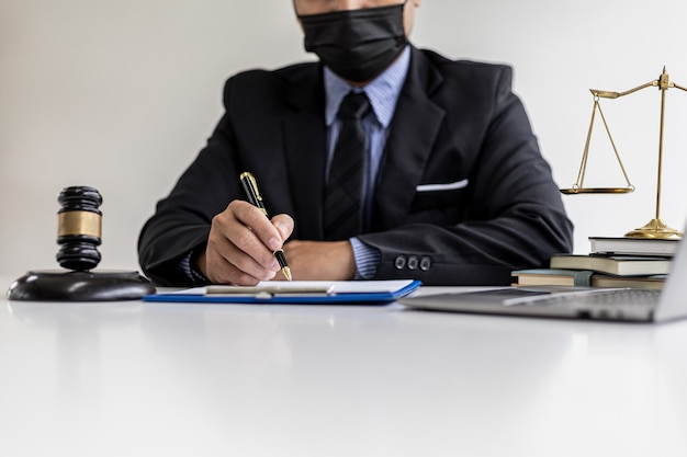 弁護士は、訴訟と戦う方法として、事件と法律の詳細をクライアントに起草しています。クライアントは詐欺弁護士に相談しました。法律専門家からの訴訟相談の概念。