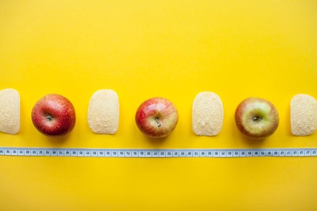 밝은 노란색 배경 체중 감량 및 다이어트에 칩과 사과 및 측정 테이프의 레이아웃